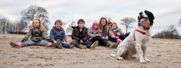 dog and children sitting on beach