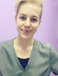 portrait of woman with short hair wearing scrubs